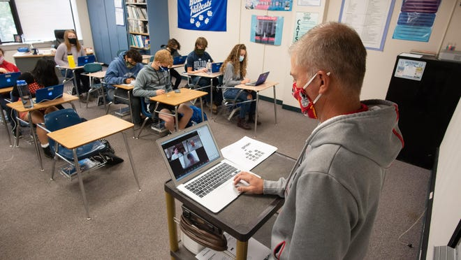 Kurt Haussler, American history teacher at Holton High School, opens up his laptop at the front of the class where three students use Zoom to virtually engage in the classroom in October. Data from the Kansas State Department of Education shows that more teachers come to Kansas than leave the state for teaching opportunities.