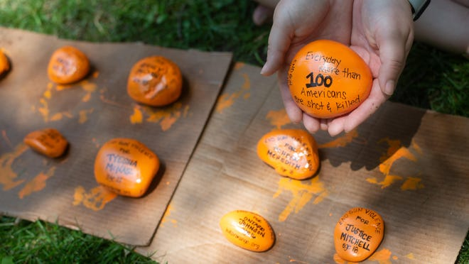 """Julie Phillips holds a stone painted orange with the message """"everyday more than 100 American are shot & killed."""" Phillips has painted about 30 stones orange with the names of people she knew who were killed by gun violence in Topeka for National End Gun Violence Week."""