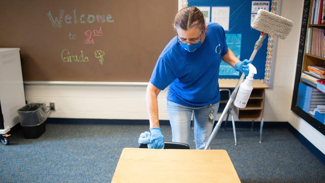 Gina Hunsperger, day custodian at Wanamaker Elementary School, wipes down a second grade classroom desk Wednesday afternoon to disinfect.
