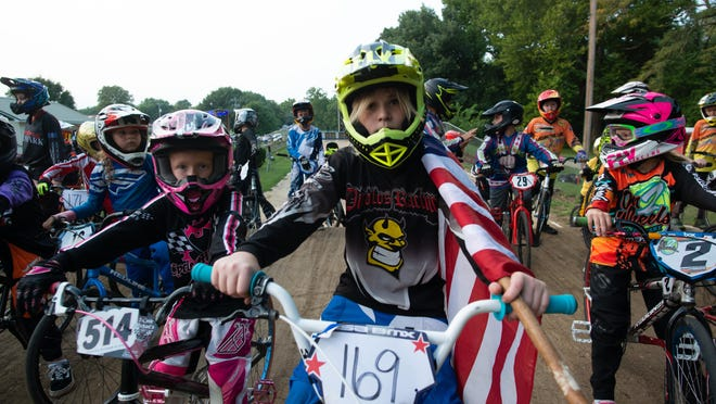 Hayden Rowlangs had the honor of holding the American flag Wednesday at Heartland Park to kick off the novice races that took place that evening.