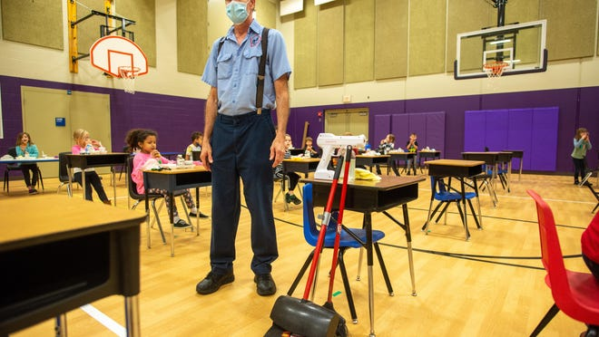 Gary Steinbock, building operator for McCarter Elementary School, pauses for a second while a class is dismissed from the lunchroom before cleaning and sanitizing a row of desks Friday morning.