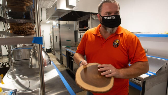 Jared Rudy, co-owner of Norsemen Brewing Co., shows off wooden slabs to be used as plates while talking about the brewery's new food offerings Thursday. Beginning Nov. 2, the brewery will begin serving food and being open seven days a week.