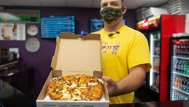 Eli Campbell, co-owner of Doughboyz Pizza at 1312 N. Kansas Ave., holds up a freshly made jalapeno popper pie Friday afternoon. The 10-inch specialty pie sells for $12.49.