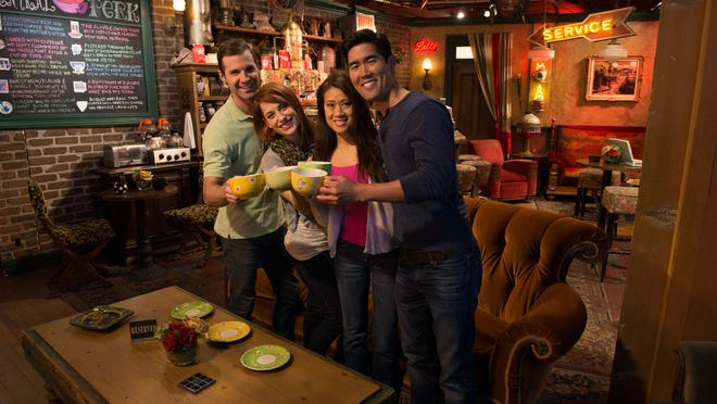 Tour goers pose in front of the famous orange couch on the set of Central Perk, the coffee shop from Friends