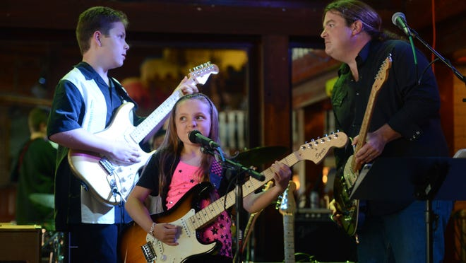 """Music students Ethan Peeler, 12, Kaelyn Peeler, 9, and Ethan Mosley, drums, perform """"Mary Had a Little Lamb"""" by Stevie Ray Vaughn with instructor Jim Brown on Wednesday at Seville Quarter during the Gulf Coast School of Music Spring 2014 Student Show."""