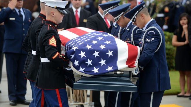 """Members of the Air Force and Marine Honor Guard carry the casket of Air Force Col. George E. """"Bud"""" Day at his funeral service at Barrancas National Cemetery."""