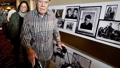 This Feb. 8, 2005 file photo, photographer Phil Stern walks past a gallery of photographs in Los Angeles, that he took of the late actor James Dean. Stern, the award-winning photographer who lugged his camera into combat during World War II and later became known for candid shots of Hollywood stars, died died Saturday in Los Angeles. He was 95.