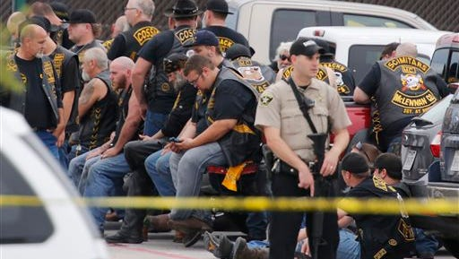 A McLennan County deputy stands guard near a group of bikers in the parking lot of a Twin Peaks restaurant Sunday in Waco, Texas.