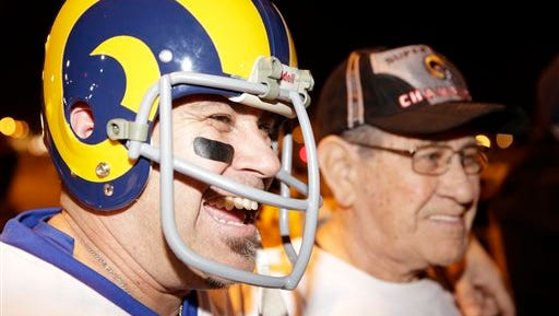 Football fans Duane Vallejos, left, and his father, Bert, a Rams fan since 1953, from Walnut, Calif., celebrate the return of their team to Los Angeles on the site of the old Hollywood Park racetrack in Inglewood, Calif.,  Tuesday, Jan. 12, 2016. NFL owners voted Tuesday night, to allow the St. Louis Rams to move to a new stadium at the site just outside Los Angeles, and the San Diego Chargers will have an option to share the facility. The Rams, based in the LA area from 1946-94, will play in a temporary facility, probably the Los Angeles Coliseum, until the new stadium is ready for the 2019 season. (AP Photo/Damian Dovarganes)