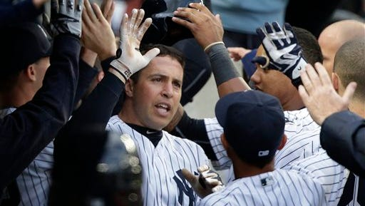 New York Yankees first baseman Mark Teixeira is greeted in the dugout after hitting a three-run home run against the Houston Astros during the seventh inning of a baseball game, Thursday, April 7, 2016, in New York. (AP Photo/Julie Jacobson)