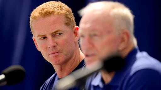 Dallas Cowboys head coach Jason Garrett, left, looks over at owner Jerry Jones, right, as he speaks at a news conference.