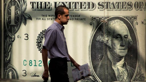 FILE - In this Thursday, Nov. 3, 2016, file photo, a man walks past a poster showing a U.S. dollar outside an exchange office in Cairo. President-elect Donald Trump's ambitious plans to revive American exports, keep jobs in the United States and encourage oil drilling face a home-grown threat: the surging U.S. dollar. Since the Nov. 8 election, the U.S. dollar has climbed to a 14-year high against the currencies of America's major trading partners. (AP Photo/Amr Nabil, File)