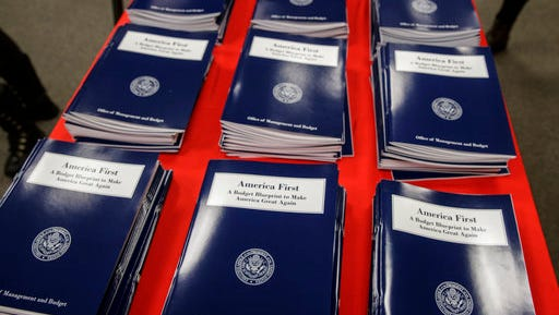 FILE - In this March 16, 2017 file photo, copies of President Donald Trump's first budget are displayed at the Government Printing Office in Washington. resident Donald Trump is proposing immediate budget cuts of $18 billion from programs like medical research, infrastructure and community grants so U.S. taxpayers, not Mexico, can cover the downpayment on the border wall.