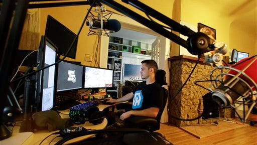 In this Nov. 6, 2014 photo, Adam Young views multiple computer screens where he plays video games for a living, in Lakeland, Fla. Young is one of three roommates that plays the games online to entertain others. (AP Photo/John Raoux)