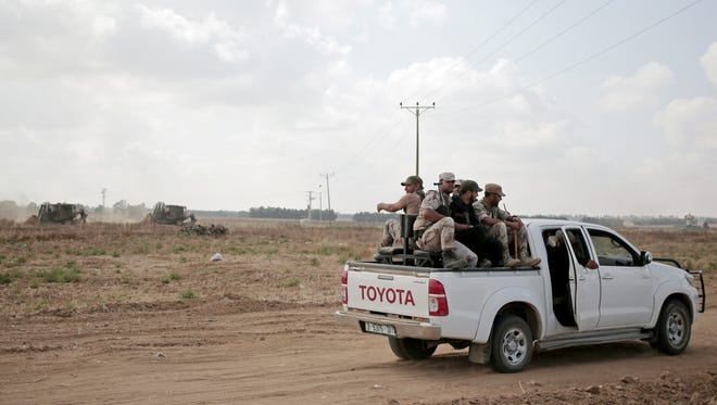 In this Wednesday, June 10, 2015 photo, Palestinian Hamas gunmen ride on the back of a pick-up truck as they patrol the border with Israel near the southern Gaza Strip town of Khan Younis, as Israeli military bulldozers are seen in the background. Nearly a year after a devastating war, Israel and Gaza's Hamas rulers appear to have formed an unspoken alliance in a common battle against the shared threat of jihadis aligned with the Islamic State group. (AP Photo/Khalil Hamra)