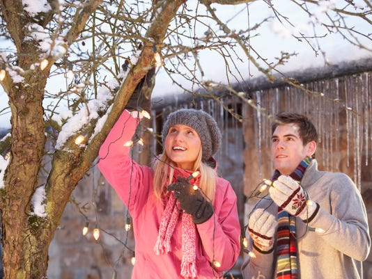 Two Teenagers Hanging Fairy Lights In Tree