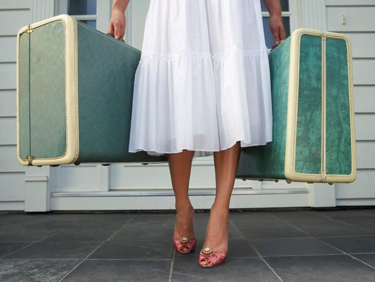 Woman leaving entrance door carrying two suitcases, low section