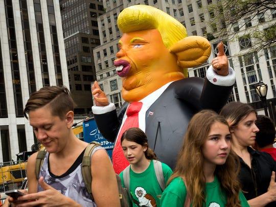 Pedestrians walk past a 15-foot tall inflatable rat