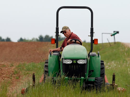 File photo from May 2016 of a farmer cutting grass along a field in Manitowoc County.