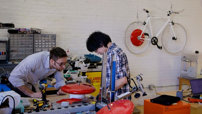 Engineers Julian Fong, right, and Jon Stevens work on a human/electric hybrid bicycle engine in Cambridge, Mass., last month.