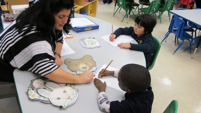 """Pre-kindergarten teacher Angela Tirone helps student Jarrell Love, 4, write a sentence about characters in the book, """"The Mitten"""" at West Hertel Academy  in Buffalo, N.Y., on Jan. 15."""