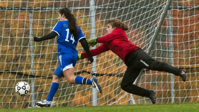 Colchester's Kelsey Cauchon (14) kicks the ball in the net past a diving CVU goalie Michaela Flore (0) for a goal during a high school girls soccer game Saturday.
