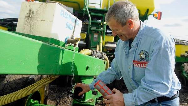 Larry Dietrich rinses a fertilizer line filter while planting corn on his farm near Elkton, S.D.