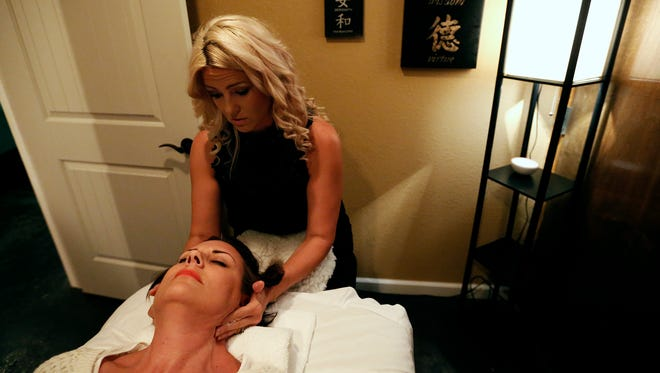 Tania Reavis, one of the co-owners of A Hip Joint, demonstrates the treatments offered by the downtown locale on her friend and costumer LaDonna Rodriguez on July 19, 2016.