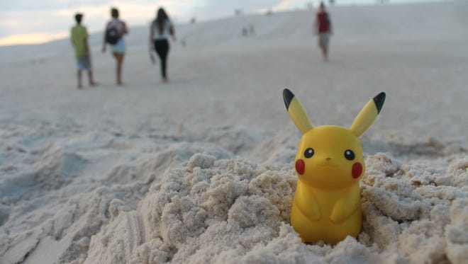 Pikachu, a character in the Pokémon world, nestles in the sand on Wednesday evening as visitors search for him and his buddies on the Pokémon Go app.