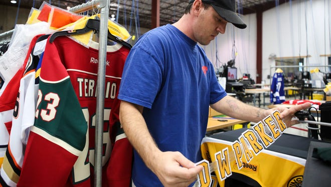 Fanatics presser Shane Coffman prepares to complete a customer's order Wednesday. Custom text and number choices are bonded to the jerseys using a heated press. Fanatics is one of the area companies looking for seasonal help.