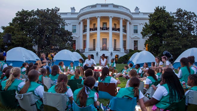 President Barack Obama and first lady Michelle Obama talk with Girl Scouts during a Lets Move! event on the South Lawn of the White House, on Tuesday, June 30, 2015, in Washington. Fifty fourth-grade Girl Scouts from councils in Maryland, West Virginia, Virginia, the District of Columbia and Oklahoma have been invited to spend the night sleeping in tents pitched on the South Lawn.