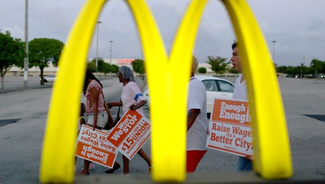 Protesters gather at a McDonald's restaurant on tax day asking for higher wages on April 15, 2015 in Miami Gardens, Florida. Fast food workers in cities around the United States joined by adjunct professors, home care, child care, airport, industrial laundry,  Walmart workers  and others are asking for higher wages and other rights for working people.