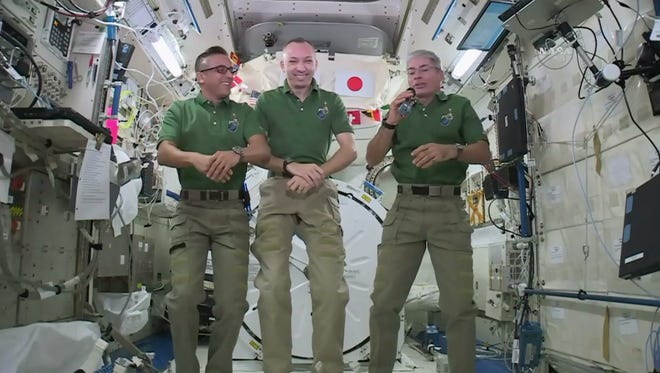 In this undated image provided by NASA,  NASA astronauts Joe Acaba, left, Randy Bresnik, center, and Mark Vande Hei give interviews on the International Space Station.