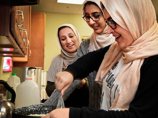 Three members of the Mufreesboro Muslim Youth group — Sarin Chamdin, left, Talea Rahman and Dana Swaies — prepare mashed potatoes for a Thanksgiving meal that was donated to those in need in 2015. The group is doing the same thing this year.