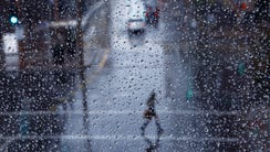 A pedestrian navigates through the rain along Central