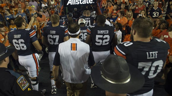 Auburn head coach Gus Malzahn walks out with Auburn offensive linemen Robert Leff (70), Xavier Dampeer (52), Tyler Carr (67) and Bailey Sharp (66) after Saturday's 29-16 loss to Texas A&M.
