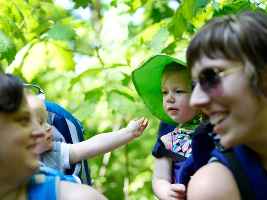 Colette Clarke of Lewisberry, left, and Carrie Soltis of Warrington Township laugh as their 1-year-old daughters  Elise Clarke and Vivian Soltis share snacks on a hike. Members of Hike it Baby say the group provides a sense of community where parents help each other out.