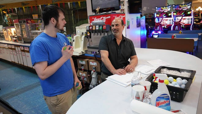Phil Santucci, Jr., a manager, talks with his father Phil Santucci, owner of Vince's Sports Center, in Newark, about future parties scheduled at their family owned business since 1981.