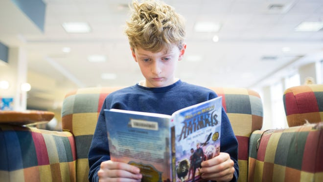 Midway Elementary School third-grader Jack Zarrouf reads Wednesday at the Anderson County Library branch in downtown Anderson.