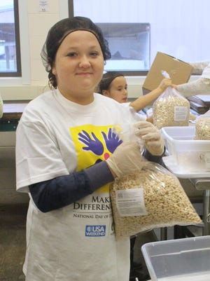 Hannah Jerzak repackages cereal at the Food Bank of the Southern Tier in this 2012 photo.