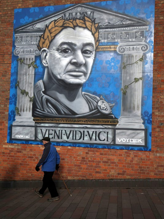 A man walks past a mural of Claudio Ranieri in Leicester city center, England, Friday, Feb. 24, 2017. There was an outpouring of dismay and incredulity when Ranieri's firing was announced on Thursday evening. He reportedly was informed of his departure by Leicester's board immediately after his return to England after the Champions League match at Sevilla, where Leicester lost 2-1 in the first leg of the last 16 on Wednesday. (Chris Radburn/PA via AP)
