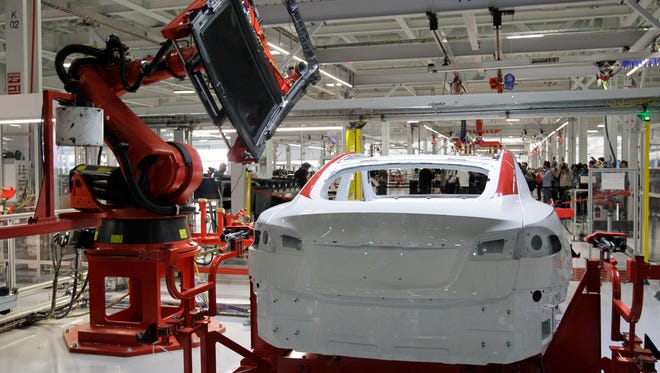 A robot puts on the top of a Tesla Model S at the Tesla factory in Fremont, Calif.,