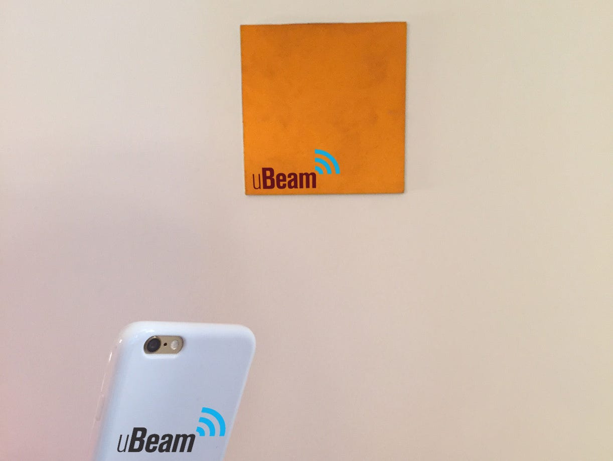 The prototype of a uBeam wireless charging transmitter, on the wall, and its hand-held receiver.