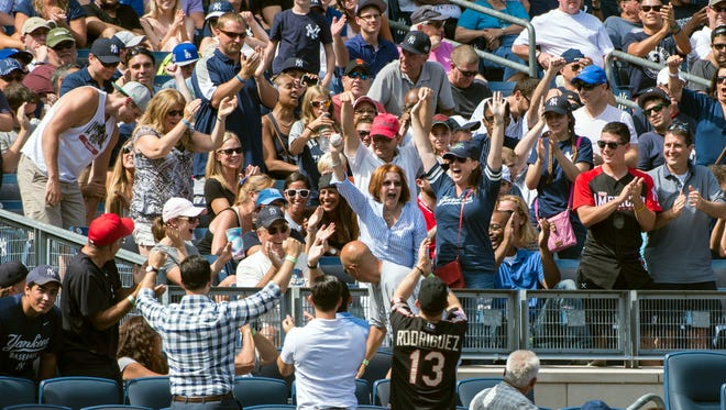 A fan grabs a foul ball during the eighth inning of the game between the New York Yankees and Toronto Blue Jays at Yankee Stadium.  The Blue Jays won 2-0.