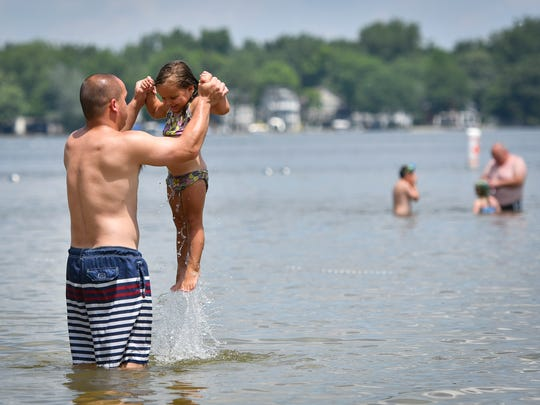 """Chris Lum of Lansing, plays with two-year-old daughter Daphne, Thursday afternoon, June 28, 2018, at Lake Lansing Park South in Ingham County.  An """"excessive heat watch"""" will be in effect for much of southwest and south-central lower Michigan, including the Lansing area, from noon Friday through Saturday night, the National Weather Service says.An """"excessive heat watch"""" will be in effect for much of southwest and south-central lower Michigan, including the Lansing area, from noon Friday through Saturday night, the National Weather Service says."""