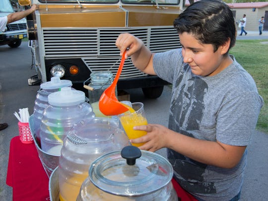 "Ivan Saenz, 13, pours a refreshing beverage known as an ""agua"" during the  Food Truck Fiesta on July 20, 2016 at Young Park."