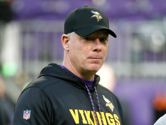 Vikings offensive coordinator Pat Shurmur stands on