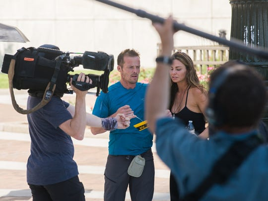 "Two contestants on ""The Amazing Race"" interpret clues on Larned Street in Detroit while filming the 31st season of the show on Tuesday, July 3, 2018."