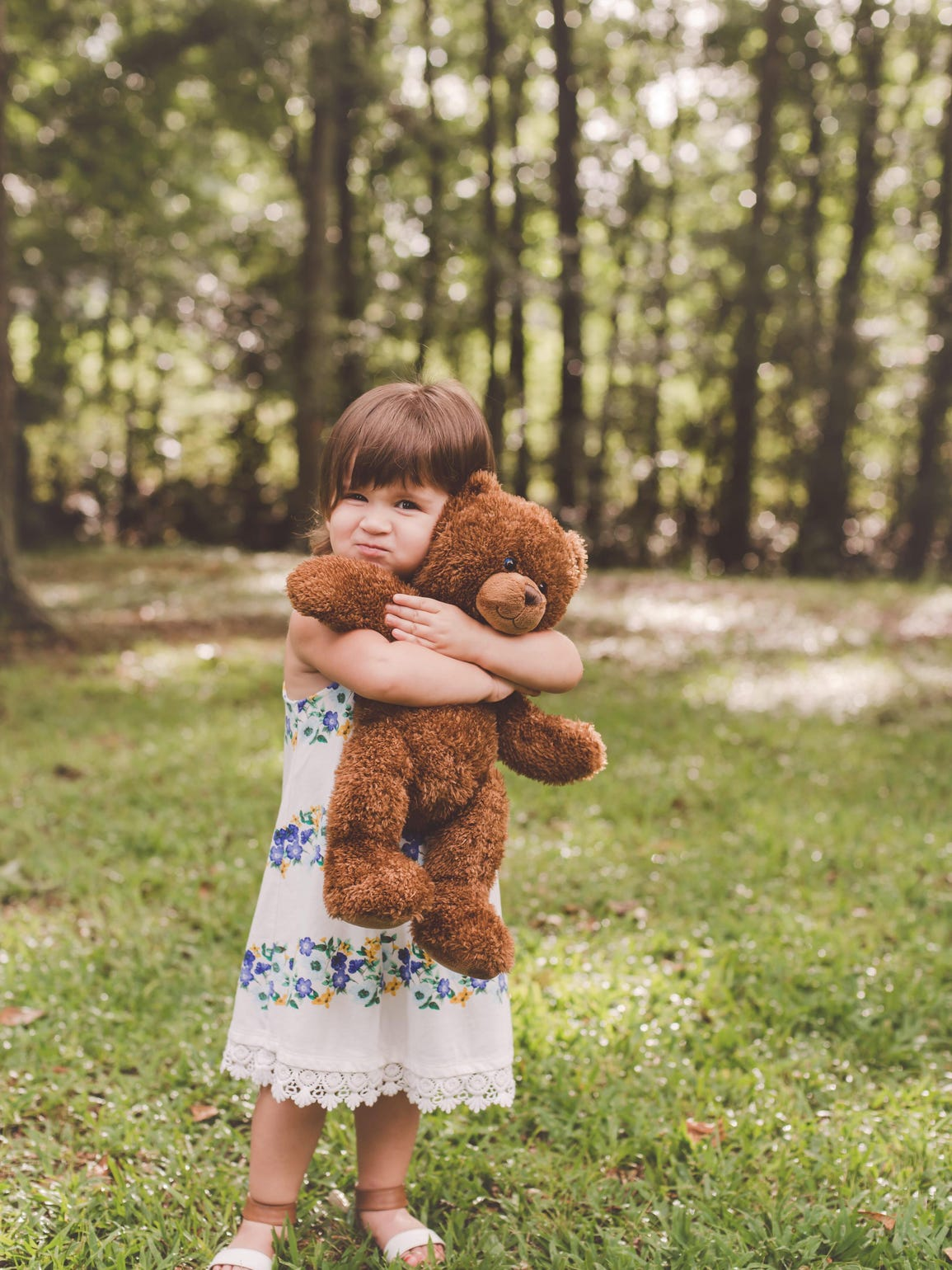 Olivia holds a bear with her baby brother's heartbeat