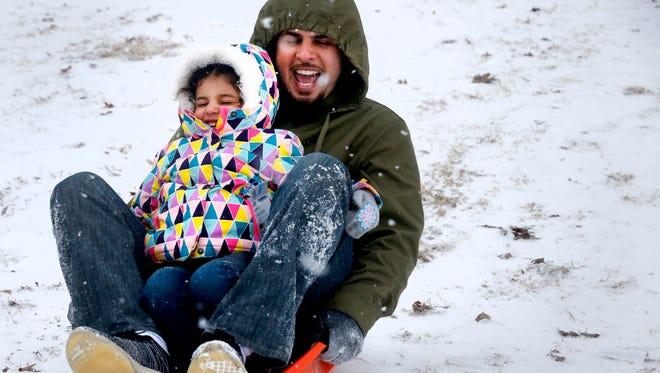 Saleh Alarifi,  slides down a hill at Barfield Park with his daughter Sara Alarifi, 4, on Tuesday Jan. 16, 2018.